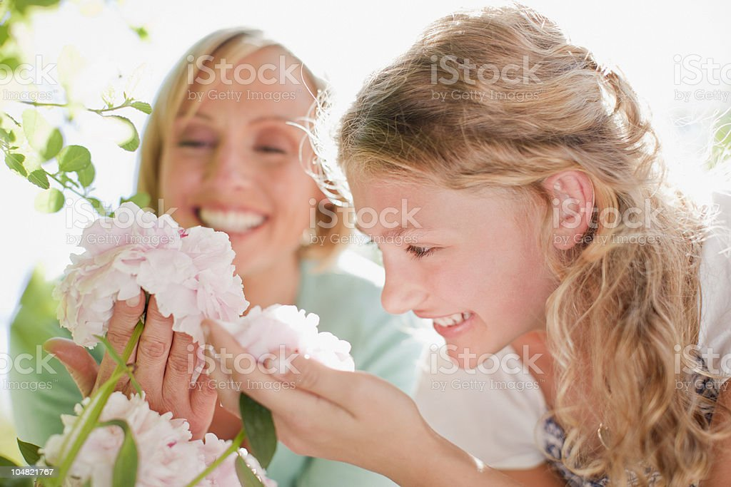 Smiling mother and daughter looking at pink flowers royalty-free stock photo