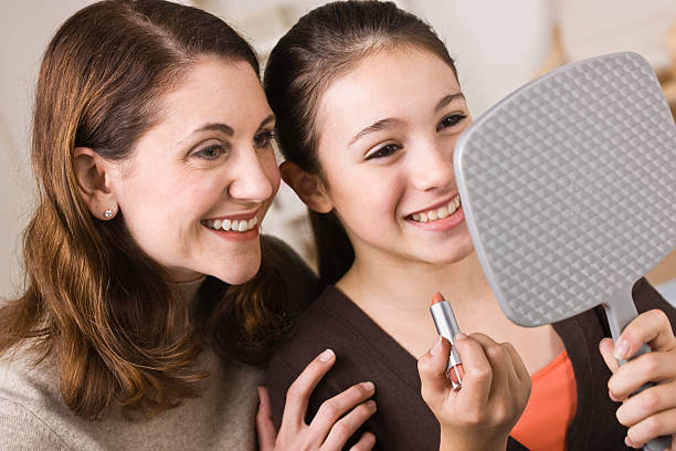 Smiling Mother and Daughter Looking into Mirror stock photo