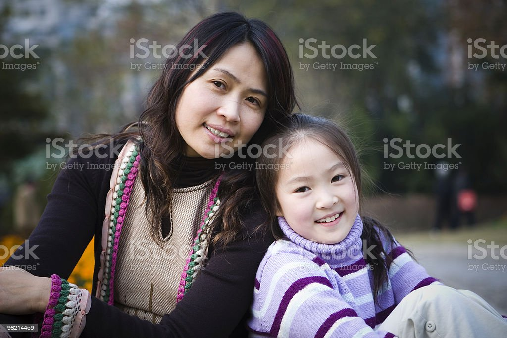 A smiling mother and daughter posing for the camera royalty-free stock photo