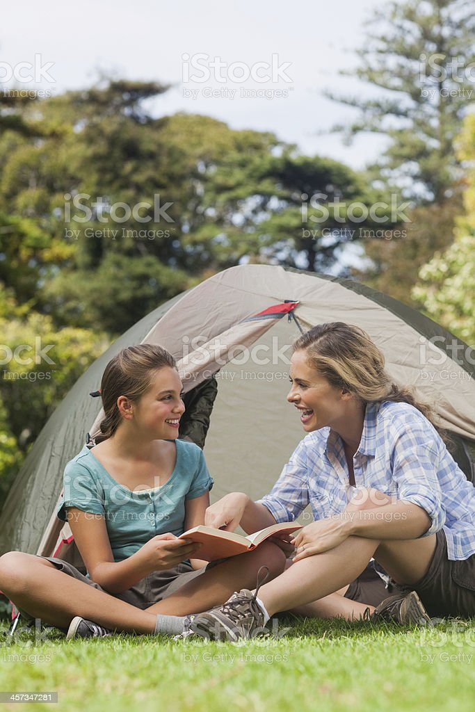 Smiling mother and daughter reading together while camping royalty-free stock photo