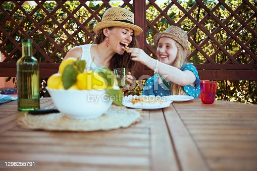 istock smiling mother and daughter sitting at table having brunch 1298255791