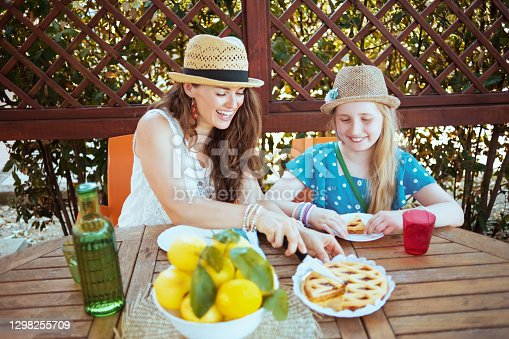 istock smiling mother and daughter sitting at table having lunch 1298255709
