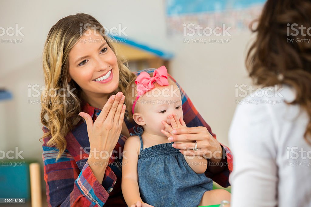 Smiling mother and her cute toddler daughter practicing sign language stock photo
