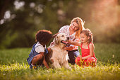 Smiling mother and her daughters cuddling retriever in nature.