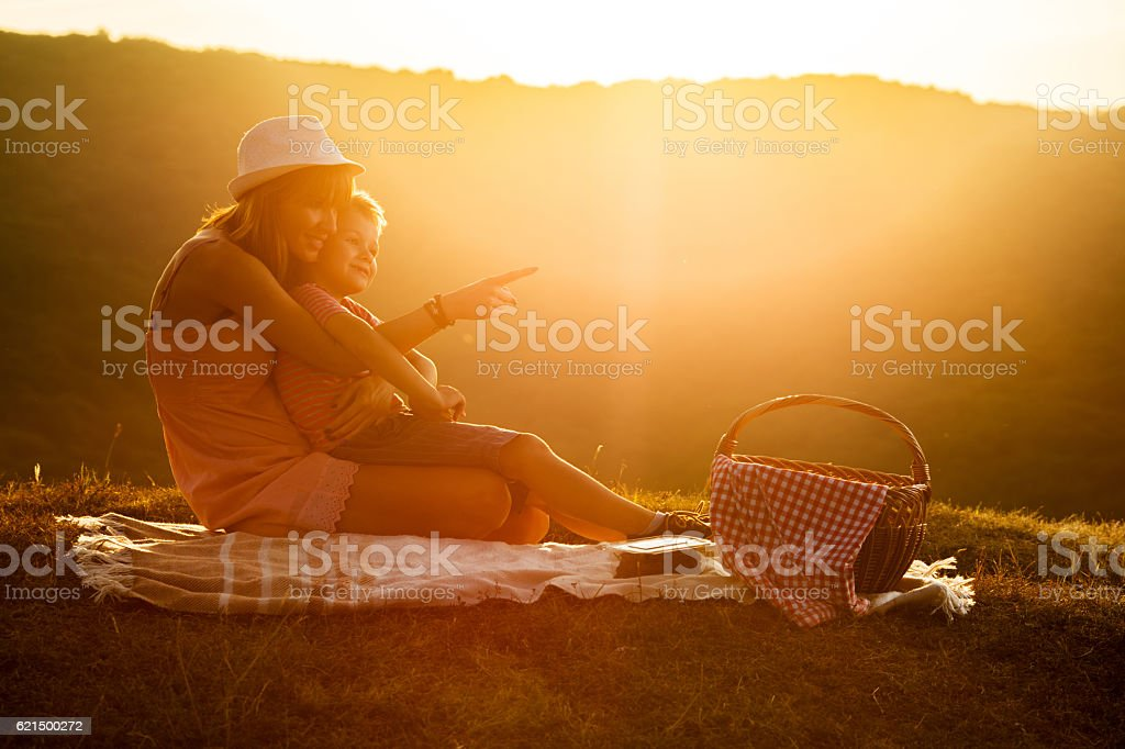 Smiling mother and son enjoying on picnic at sunset. Lizenzfreies stock-foto