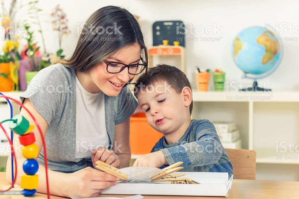 Smiling Mother and Son Playing and Learning Together at Home stock photo