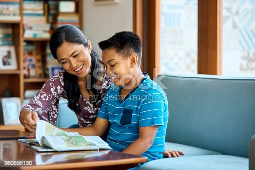 istock Smiling mother and son reading book at home 960595130