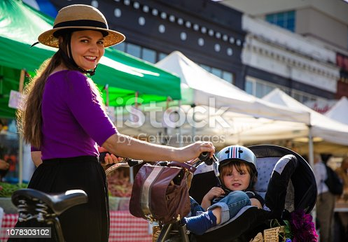 A fashionably dressed woman shops at an open air farmer's market in San Francisco with her toddler in a child seat strapped to a cargo bike.