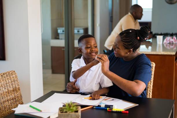 Lächelnde Mutter hilft Sohn bei den Hausaufgaben zu Hause – Foto