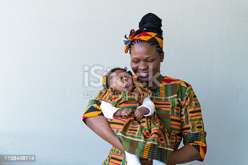 Smiling woman carrying toddler baby girl while standing against wall. Mother looking at cute daughter yawning. They are wearing traditional clothing.