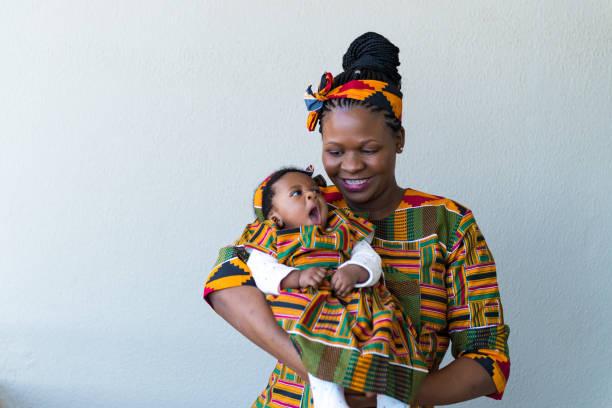 Lächelnde Mutter trägt süße Tochter gegen Wand – Foto