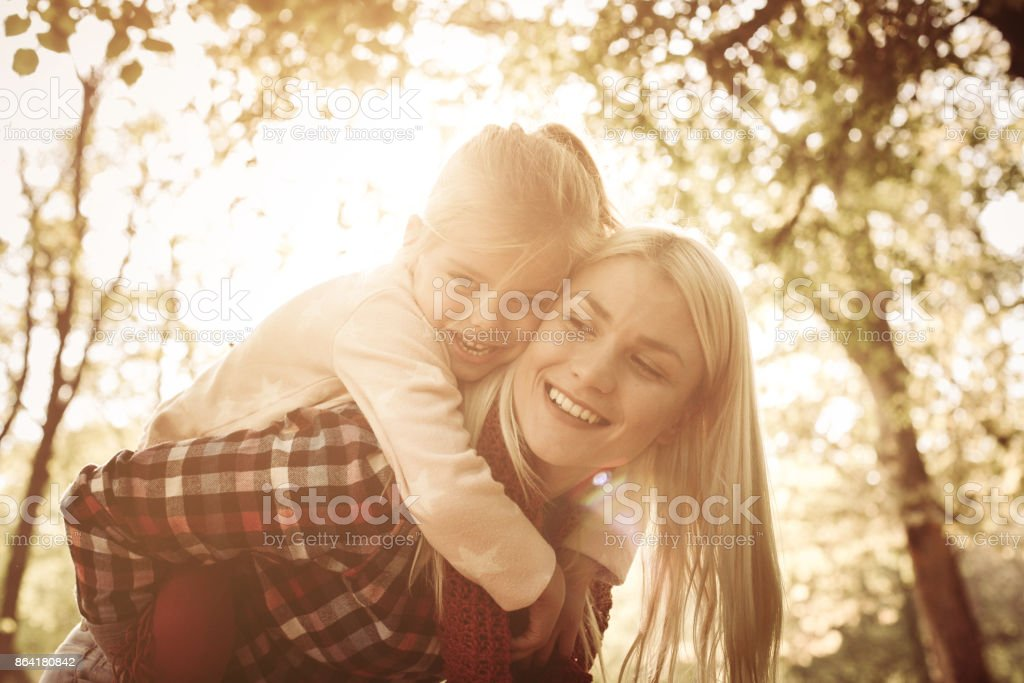Smiling mother carrying her daughter on piggyback and enjoying in nature. royalty-free stock photo