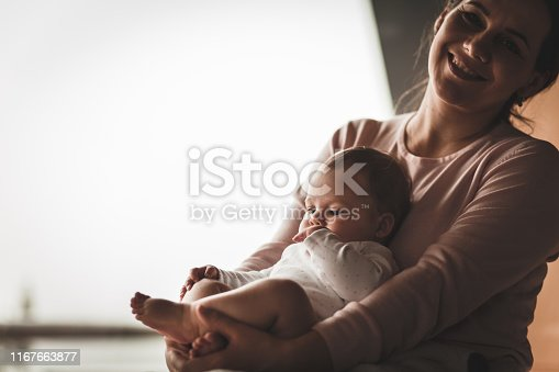 Copy space shot of affectionate mother having bonding moments while holding her little baby daughter in her lap and cuddling her. She is smiling and looking at camera.