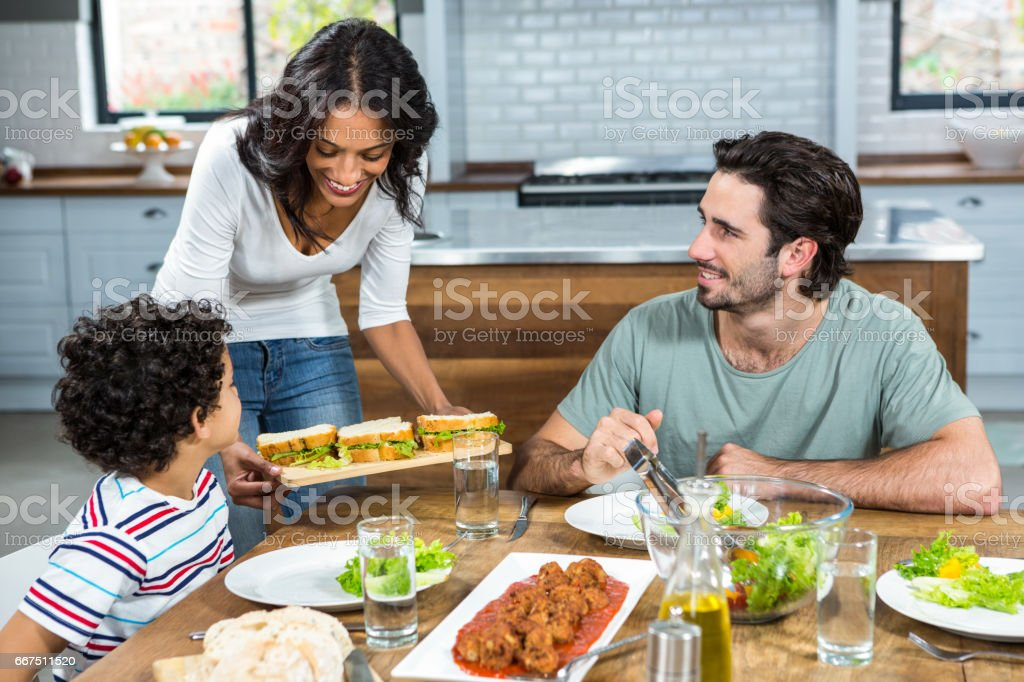 Smiling mother giving sandwiches to her son and husband foto stock royalty-free