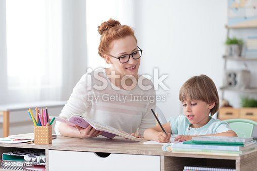 istock Smiling mother helping son 843565782