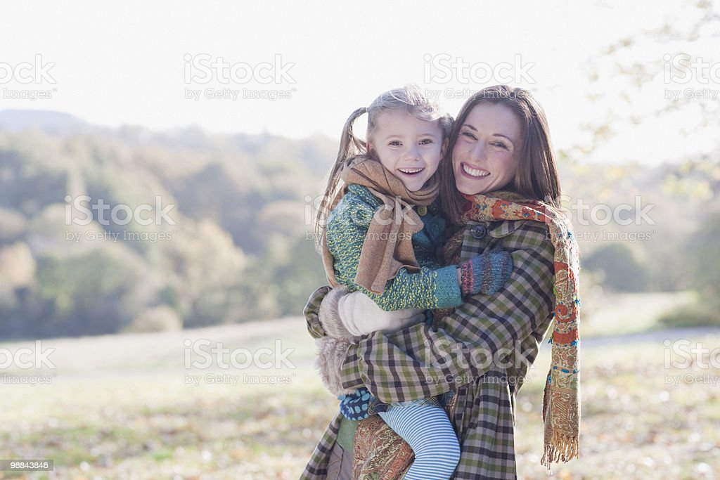 Smiling mother holding daughter royalty free stockfoto