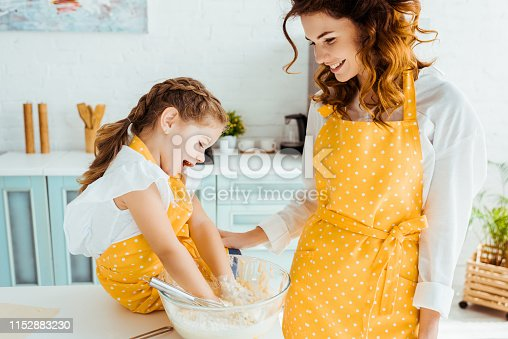 smiling mother looking at happy daughter putting hands in bowl with dough
