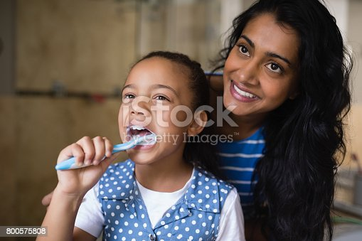 800444456 istock photo Smiling mother standing by daughter brushing teeth in bathroom 800575808