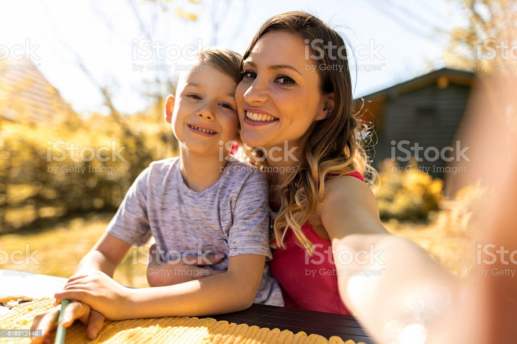 Smiling mother taking selfie with her little boy in backyard. stock photo
