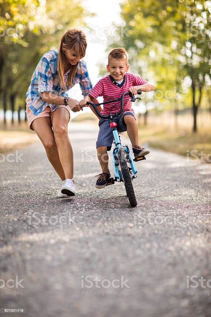 Smiling mother teaching her son to ride bicycle in nature. photo libre de droits