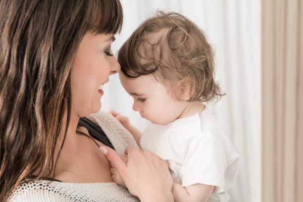 lächelnde mutter mit babymädchen. tochter in der nähe von liebevolle mutter. - scyther5 stock-fotos und bilder