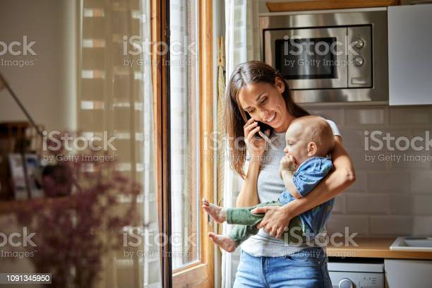 Smiling mother with baby talking on phone at home picture id1091345950?b=1&k=6&m=1091345950&s=612x612&h=6pqmjxricnkcs8thcjvcox3hwfzd8ocduvbhtk7gze8=