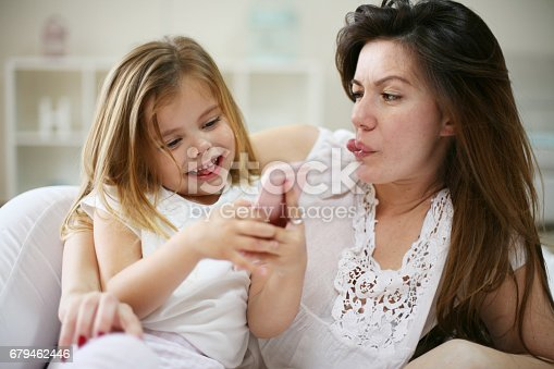 istock Smiling mother with daughter using smart phone on bed. 679462446