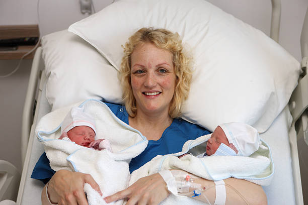 Smiling Mother With Newborn Twins In Hospital stock photo