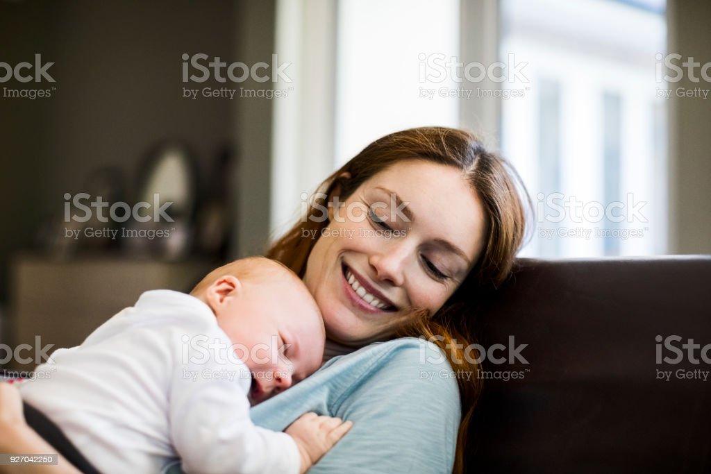 Lächelnde Mutter Mit Dem Neugeborenen Sohn Auf Dem Sofa Schlafen