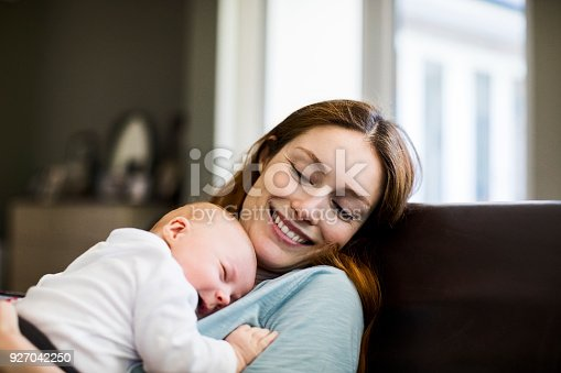 istock Smiling mother with sleeping newborn son on sofa 927042250