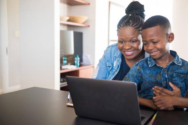 Lächelnde Mutter mit Sohn mit Laptop zu Hause – Foto