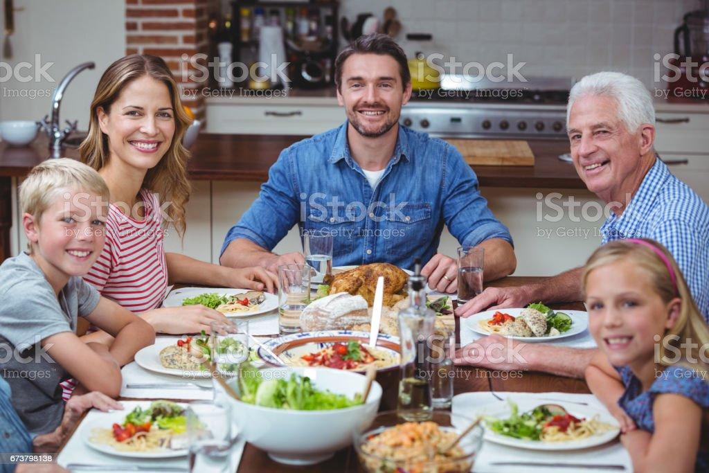 Souriant multi génération famille assis à table à manger photo libre de droits