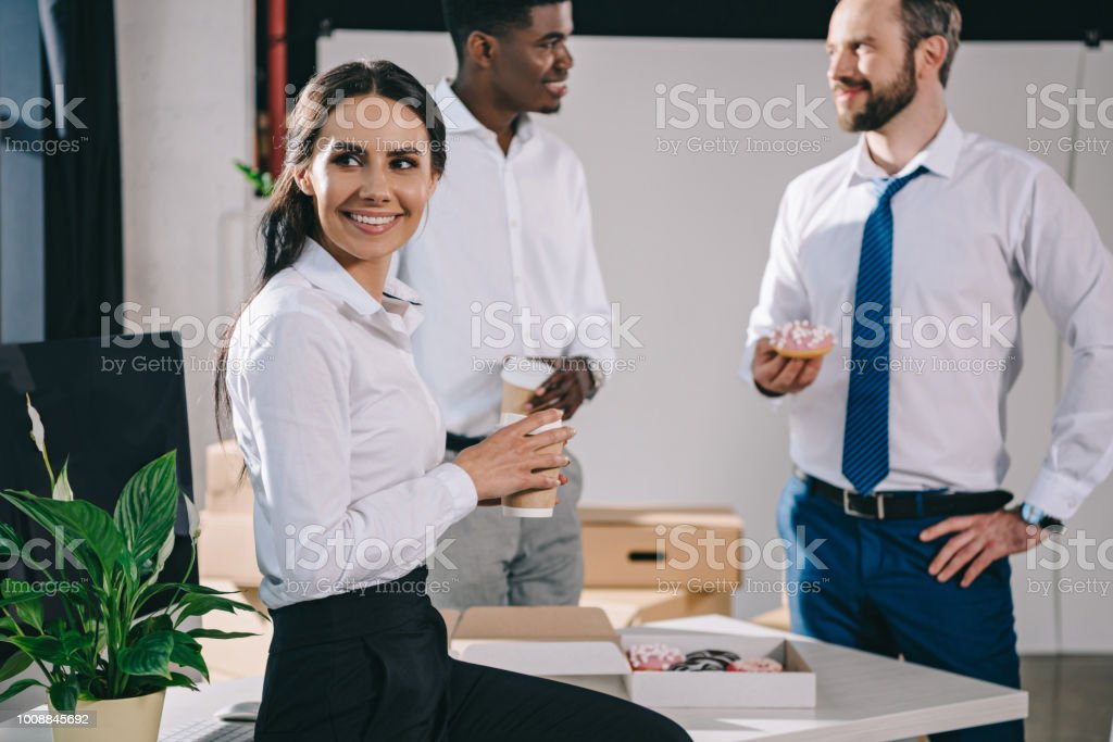 smiling multiethnic colleagues having coffee break in new office during relocation stock photo
