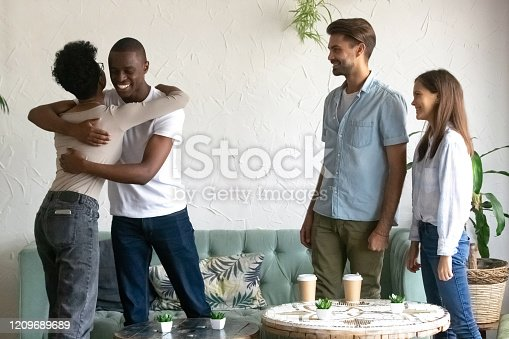 Happy multiracial young people sit in coffeeshop meet new african American girl get acquainted, smiling diverse young friends hang out in cafe hug greeting introducing to company. Friendship concept