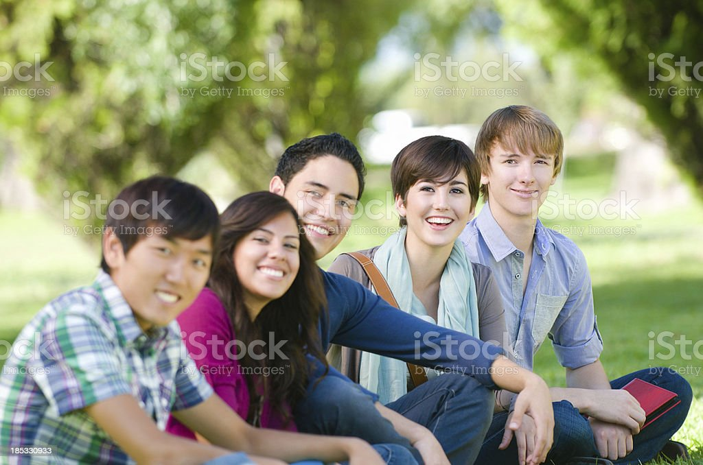 Smiling multiethnic friends seated outdoors royalty-free stock photo