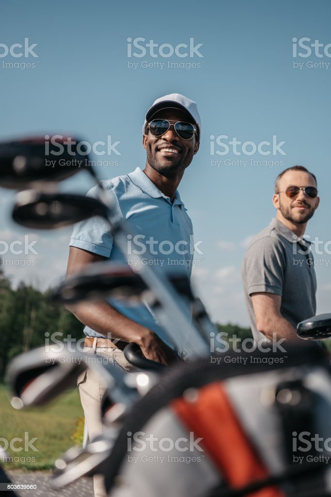 smiling multiethnic sportsmen going to the golf course, bag with clubs on foreground stock photo