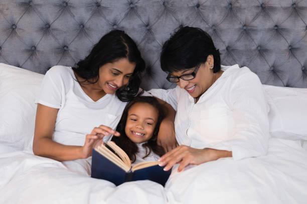 lächeln mehr-generationen-familie buch beim stillstehen auf bett - kurzgeschichten stock-fotos und bilder