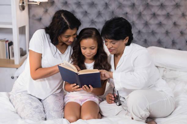 lächeln mehr-generationen-familie buch sitzend auf bett - kurzgeschichten stock-fotos und bilder