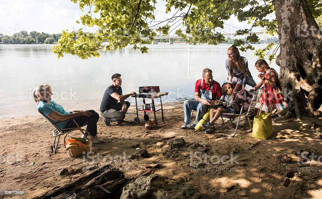 Smiling multi-generation family spending their weekend by the river. stock photo