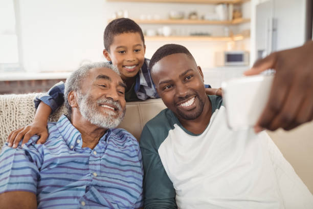 Smiling multi-generation family taking selfie from mobile phone in living room stock photo