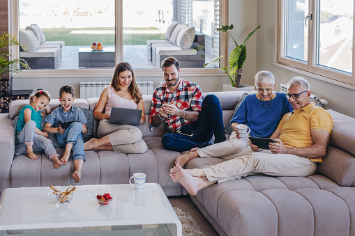 Smiling multi-generation family using wireless technology while relaxing in the living room.