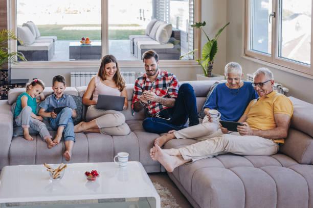 lächelnd mehr-generationen-familie per funk-technologie beim entspannen im wohnzimmer. - seniorenwohnungen stock-fotos und bilder