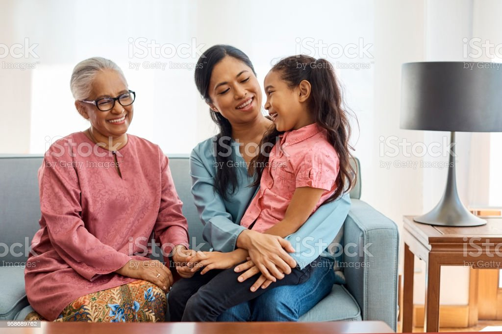 Smiling multi-generational family sitting at home stock photo