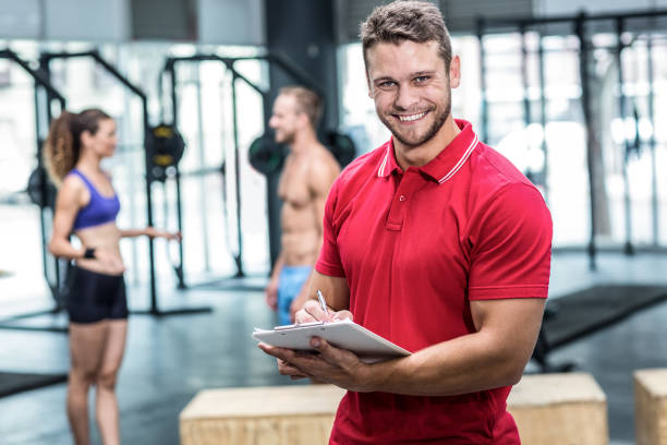 Smiling muscular trainer writing on clipboard stock photo