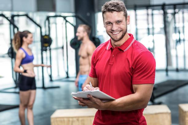 sonriente entrenador muscular en portapapeles - entrenador personal fotografías e imágenes de stock