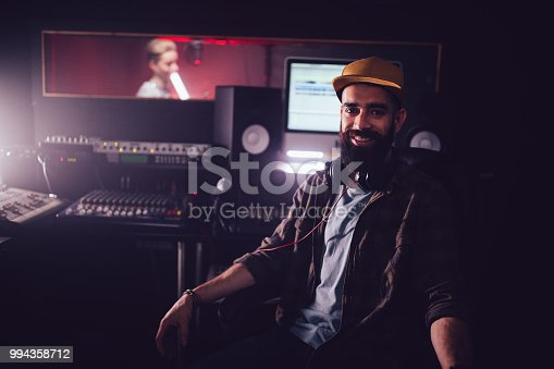 Happy sound engineer having fun working in professional music recording studio with singer