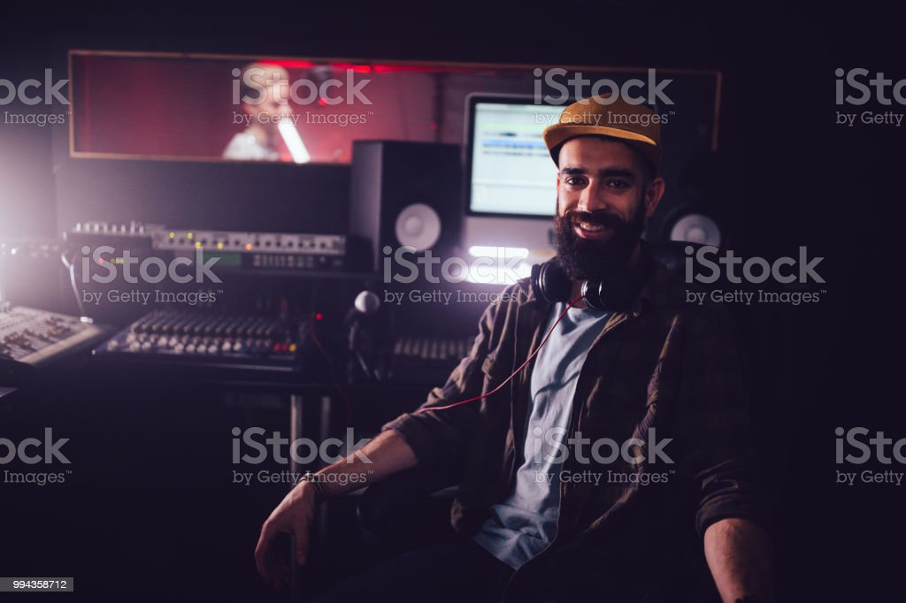 Smiling music producer working in recording studio with music artist stock photo