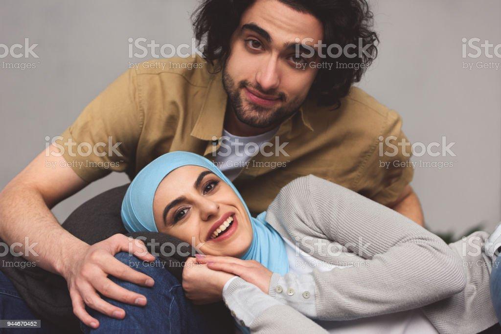 smiling muslim couple looking at camera at home stock photo