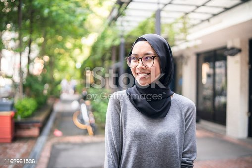 Young Muslim woman in city street.