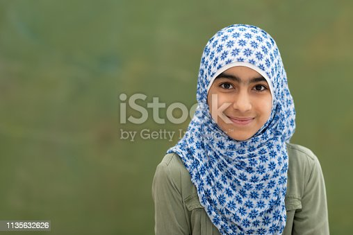 A cute little muslim girl smiles as she looks into the camera in this portrait. She is standing in front of a blackboard.